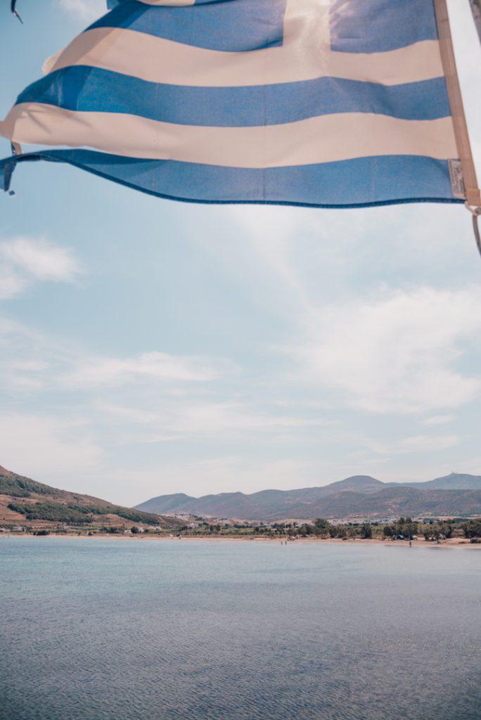 Greek flag waving over the beach