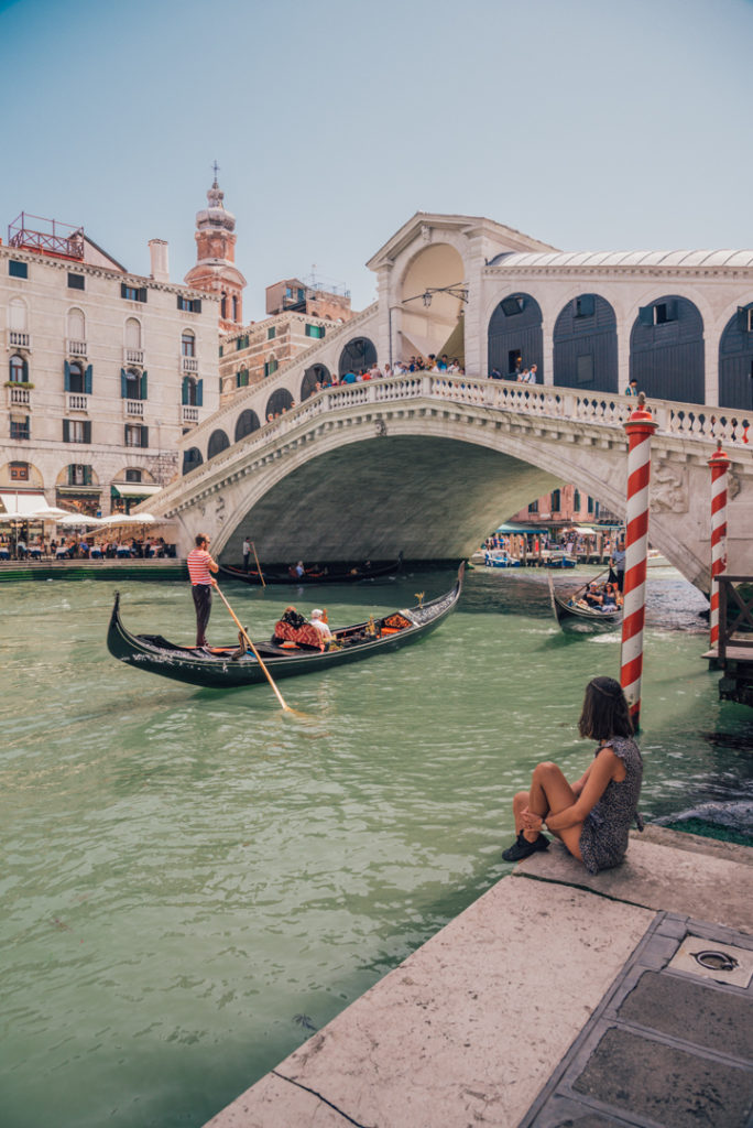 Woman relaxing by the Ponte di Rialto in Venice Italy