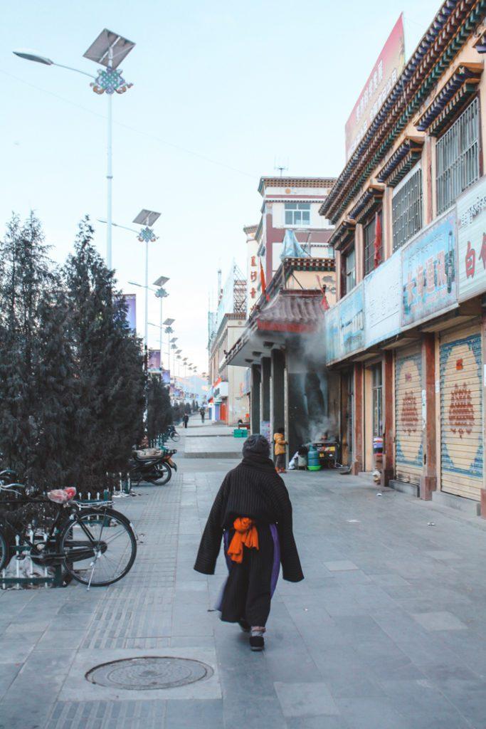 Tibetan woman walking down the street in XIahe