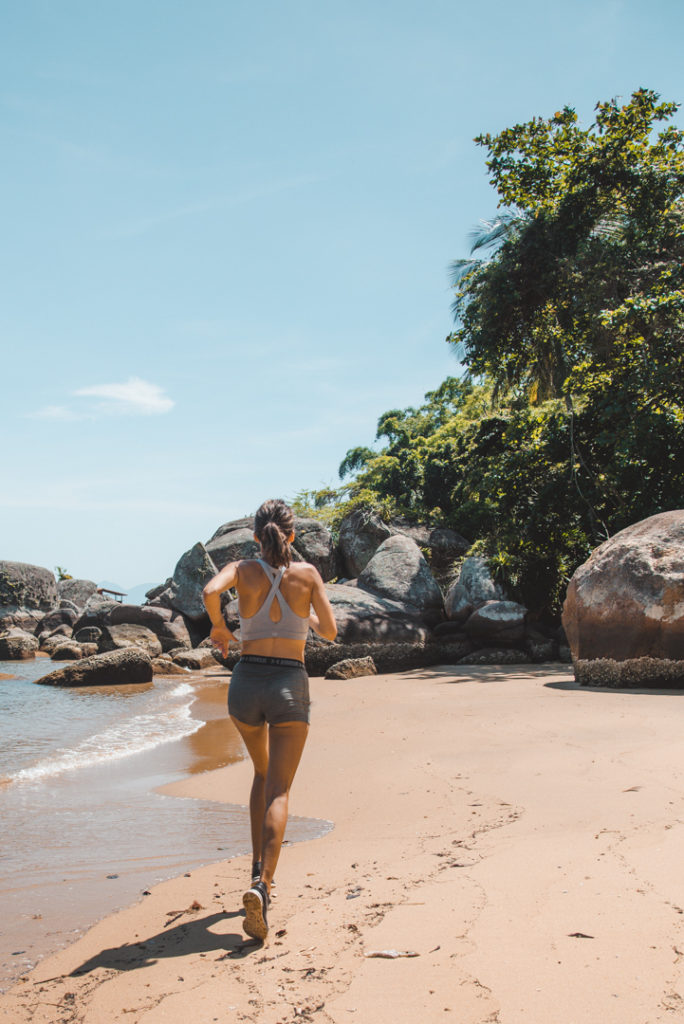 Woman jogging on the beach- self care ideas pdf