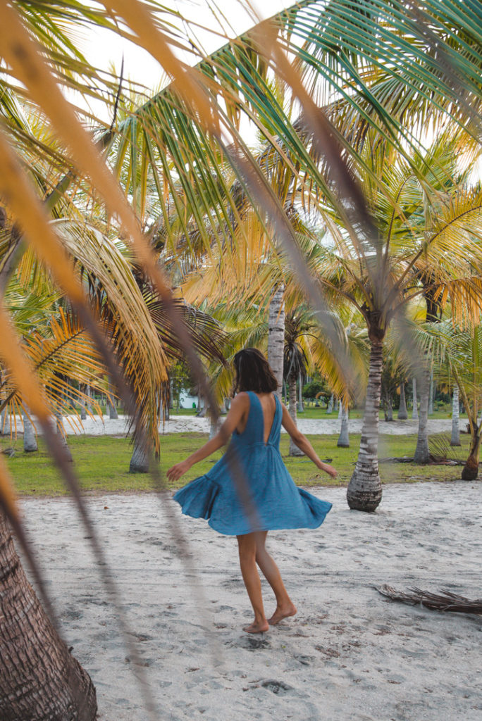 Girl twirling on the beach in Colombia