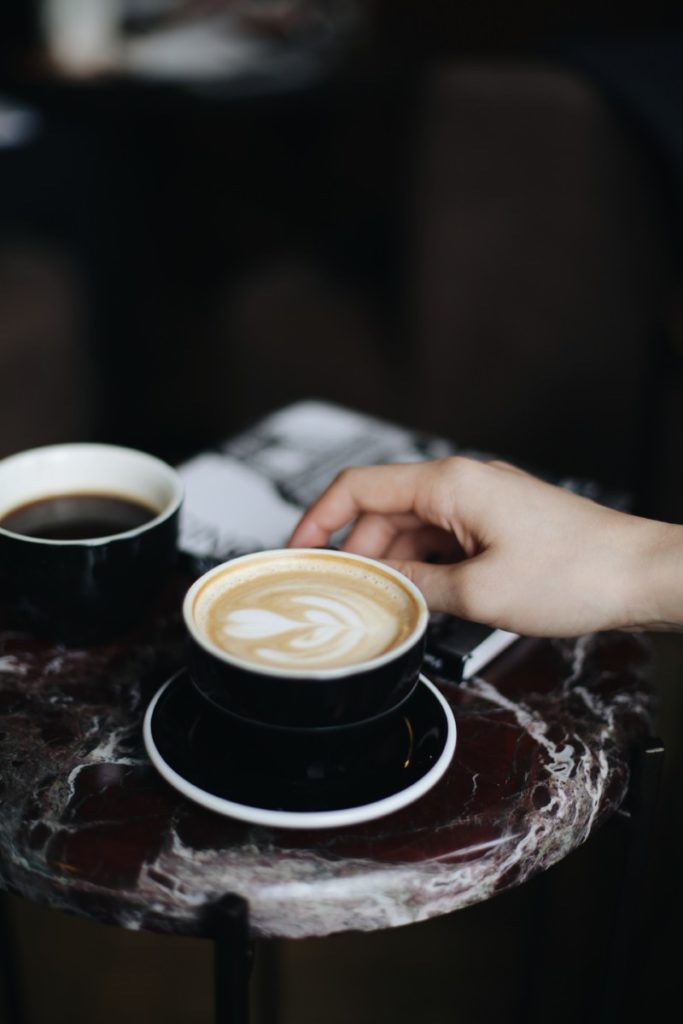 person holding a black coffee mug