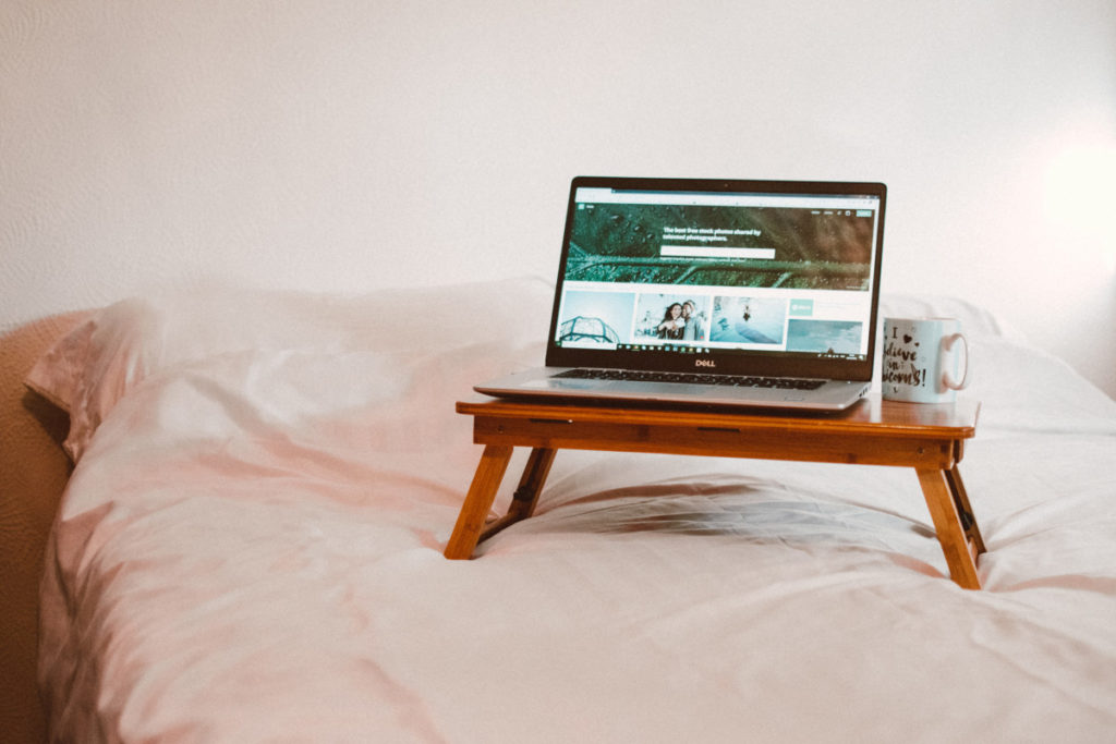 Laptop on a table in bed.