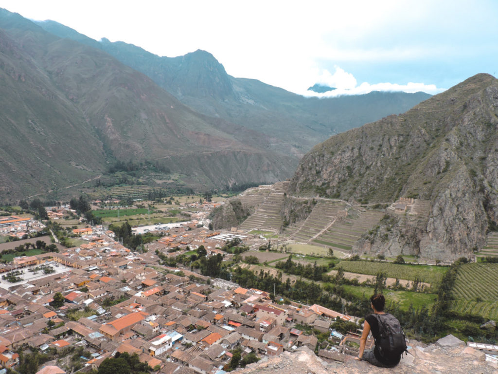 Woman sitting on top on a hill over Ollantaytambo