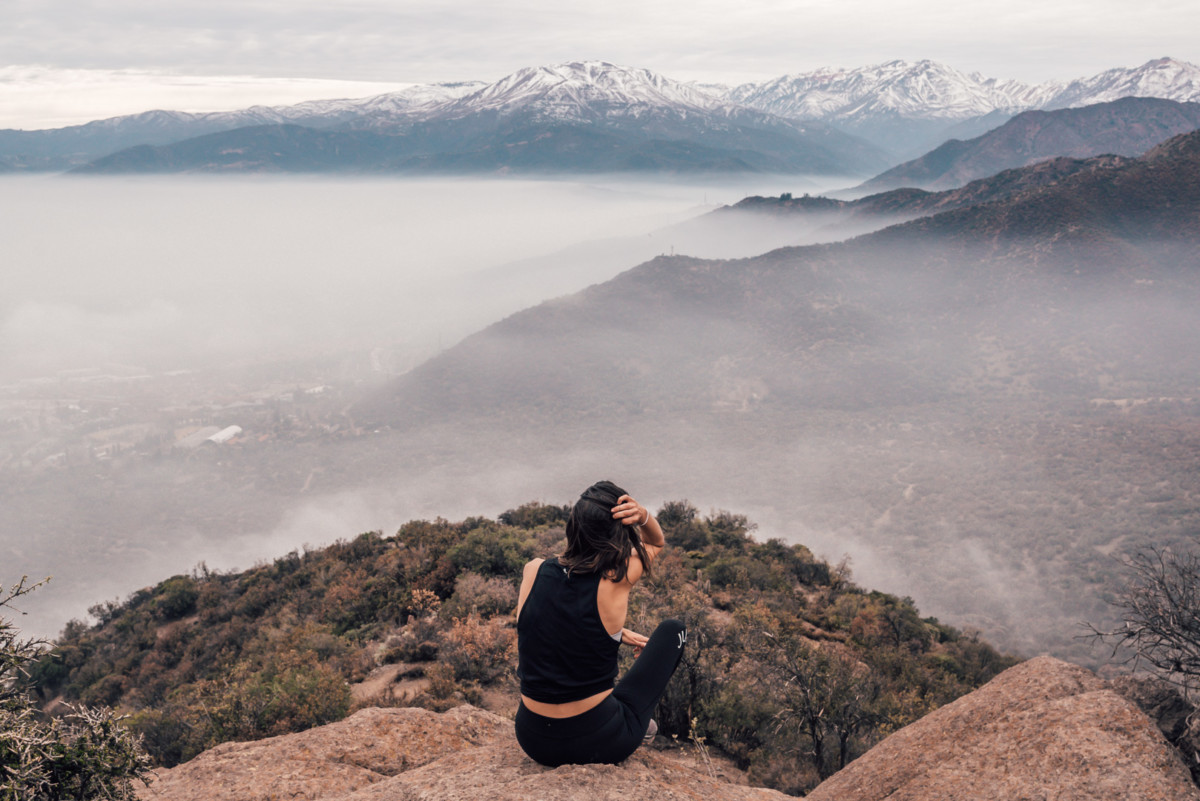 Woman sitting on top of a hill looking at the view below