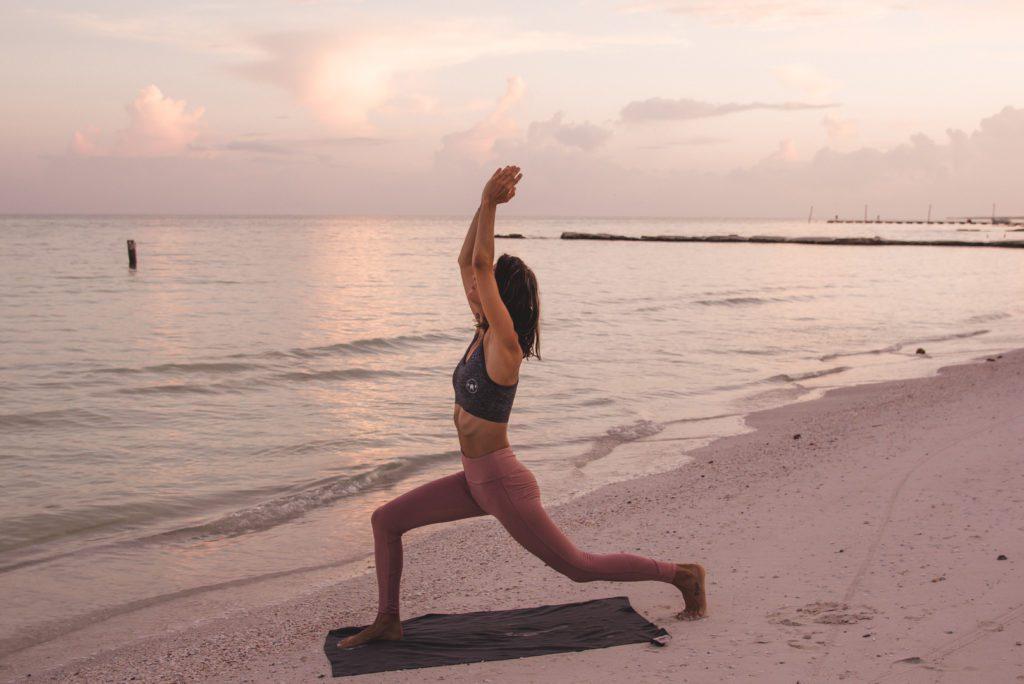 Woman doing yoga on the beach at sunrise