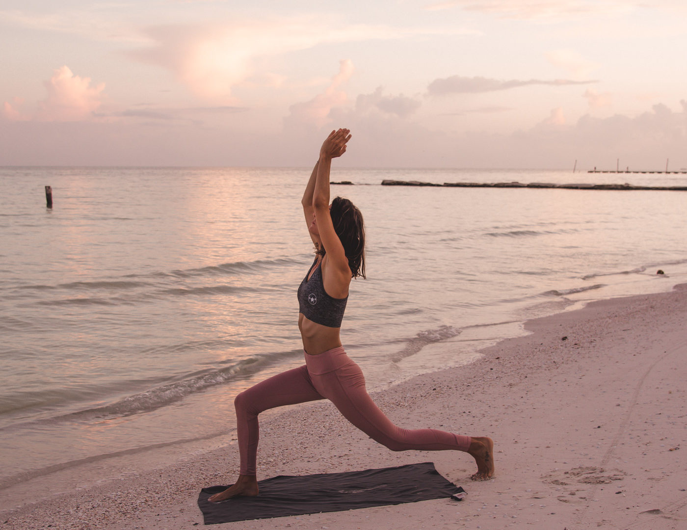 Woman doing yoga on the beach at sunrise