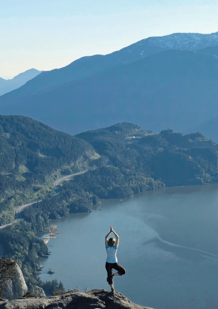 Woman doing yoga on top of a mountain