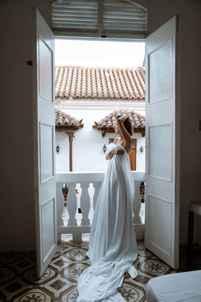 Woman looking out from a window in colonial room in Cartagena