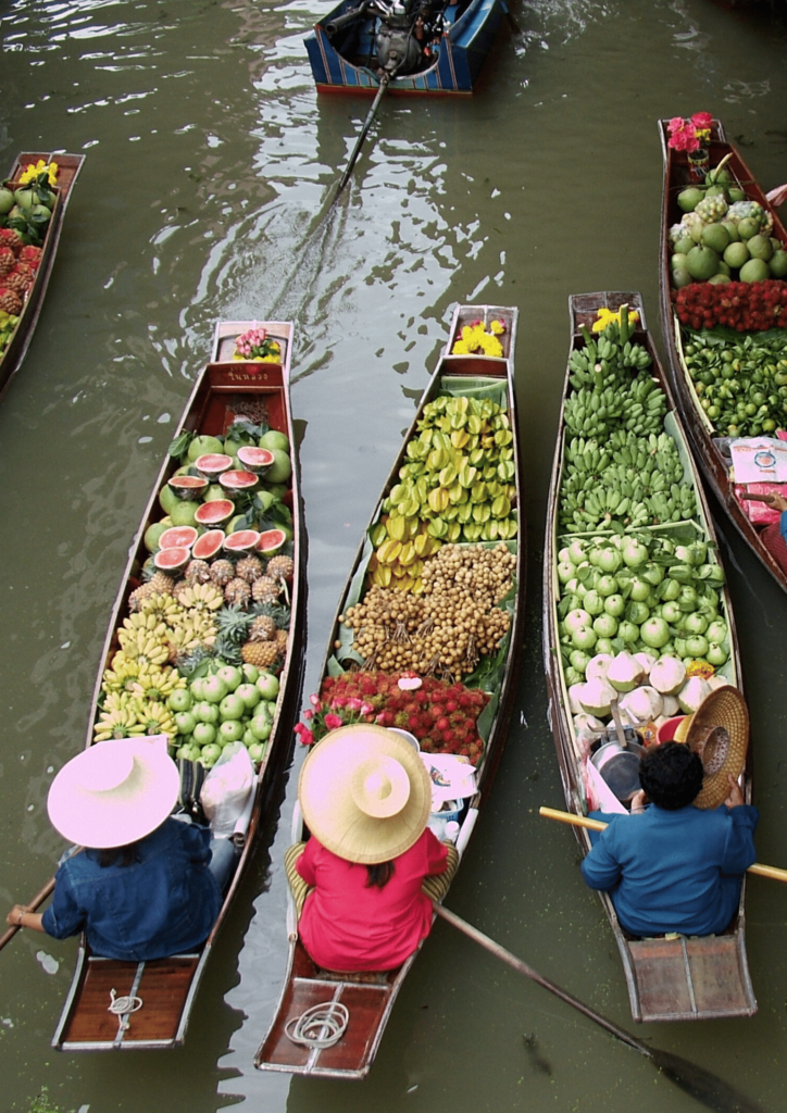 Three sellers in their boats selling fruit in Bangkok