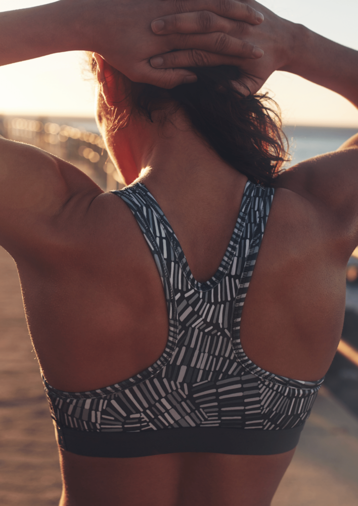 woman in a sports bra on a pier at sunset