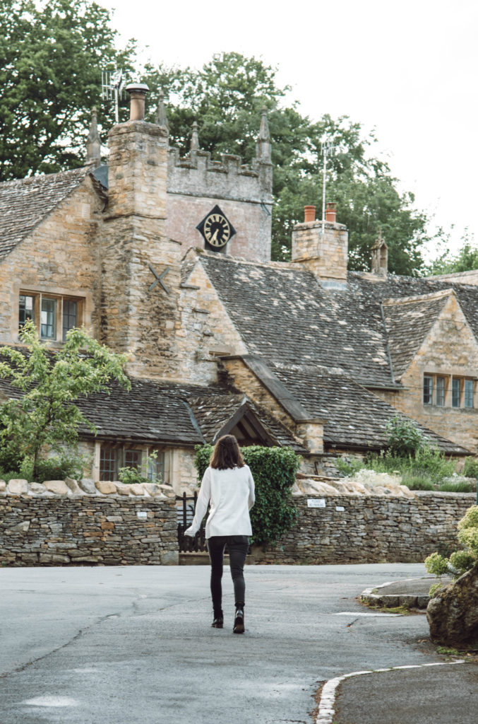 woman in a Cotswolds village with stone cottages