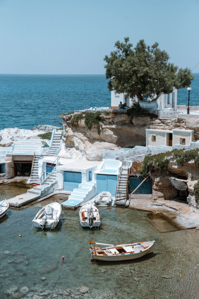 Cove with boats and boat houses on Milos, Greece