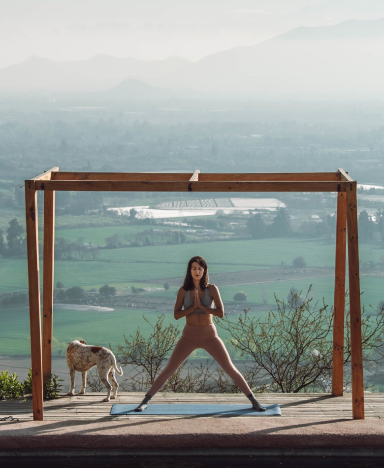 woman doing yoga on a deck with a view