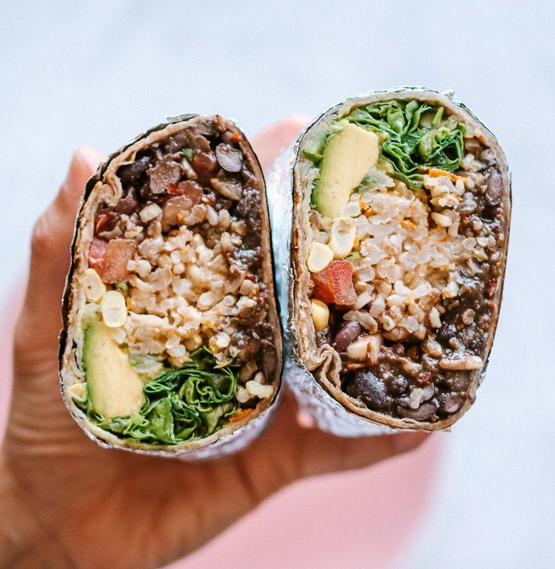 woman holding a vegan burrito