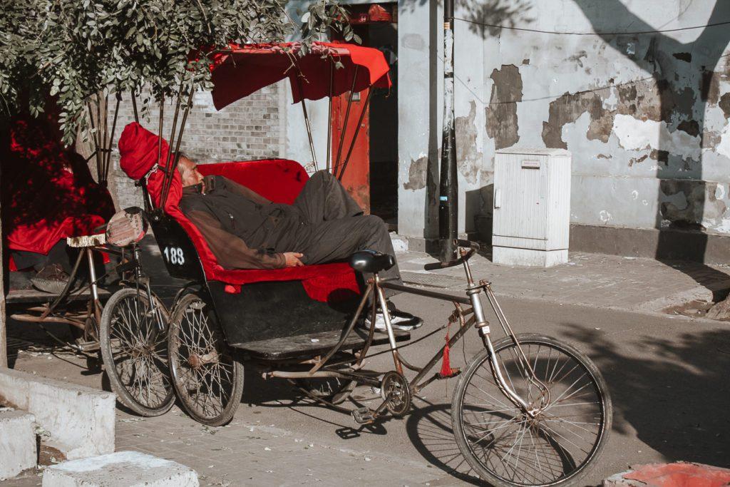 Man sleeping on a rickshaw in beijing