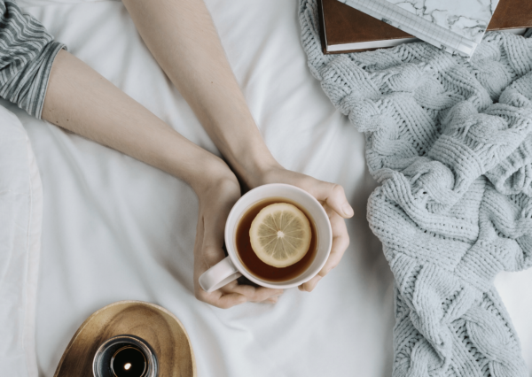 woman holding a mug of tea on the bed