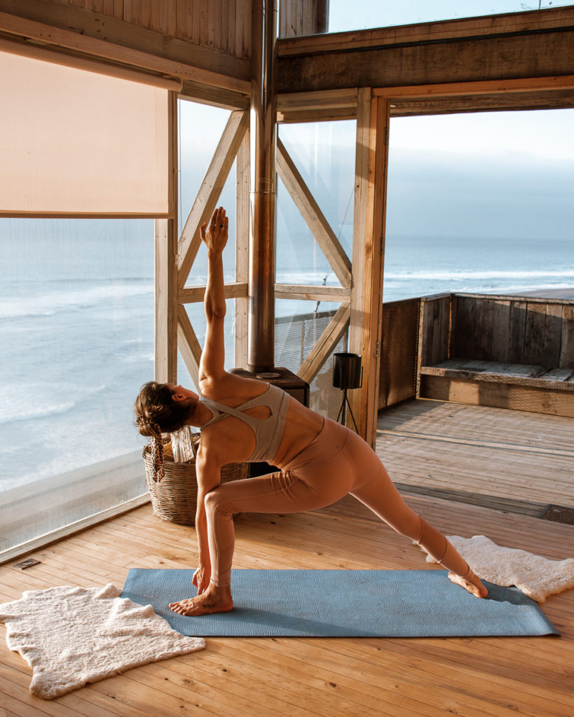 woman doing yoga in a wooden cabin by the sea- mindful morning routine