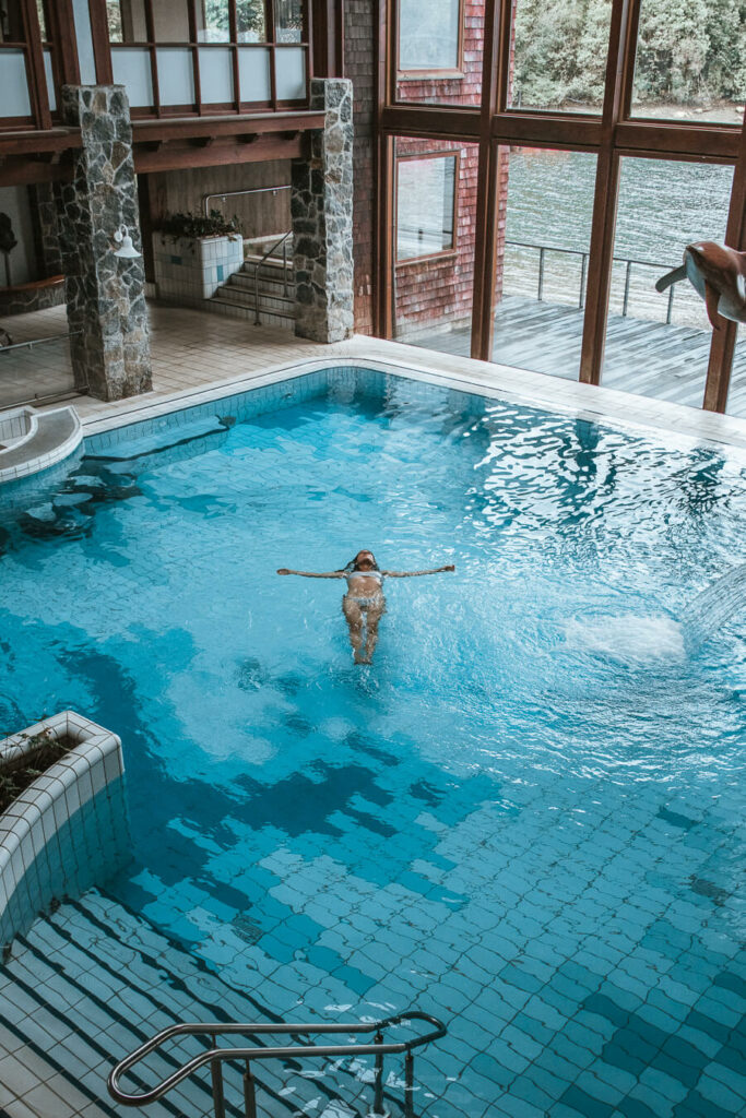 woman floating in a pool in Puyuhuapi lodge and spa