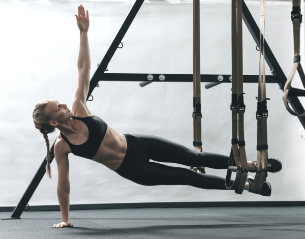 women working out with TRX- best portable exercise equipment