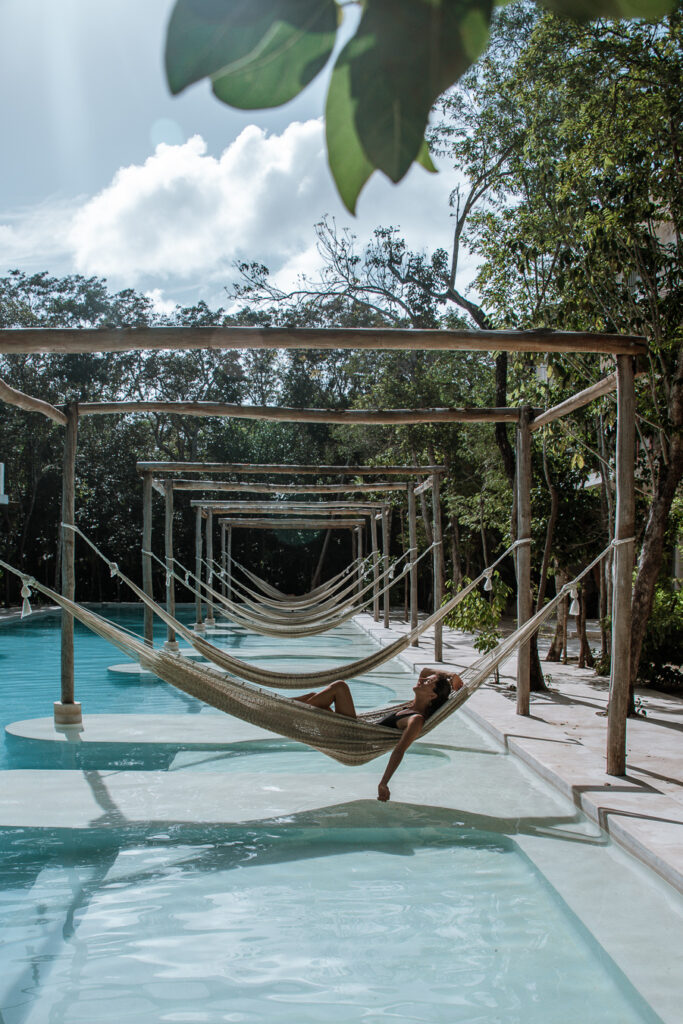 Woman on a hammock over pool a Holistika Tulum