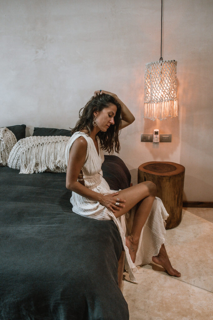 Woman sitting on bed in boutique hotel in Tulum Mexico