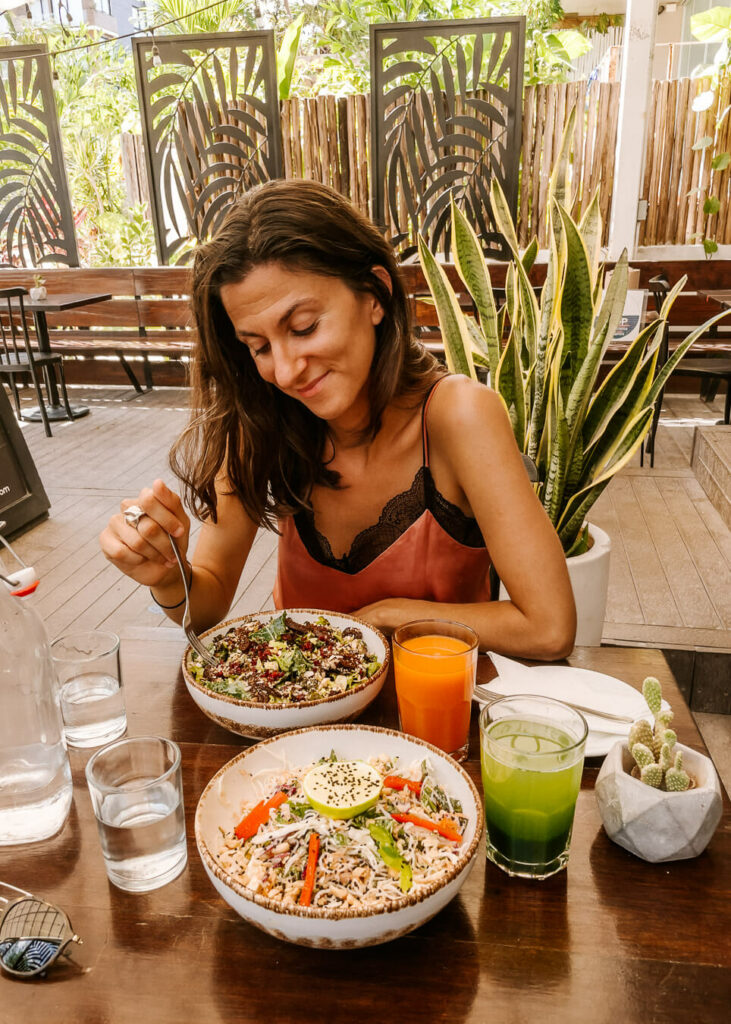 woman eating healthy food at the best vegan restaurants in playa del carmen