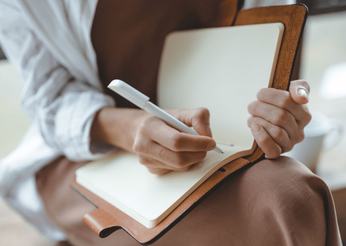 woman journaling in a notebook on her lap- self care journal prompts