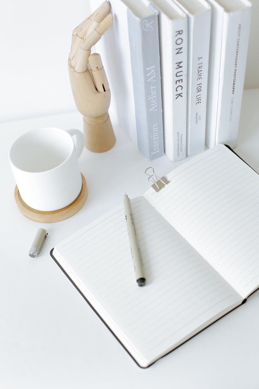 notebook opened on desk near books