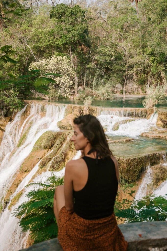 Woman sitting by a waterfall Huasteca Potosina