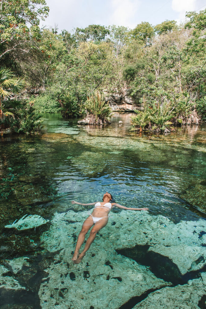 woman floating in cenotes azul
