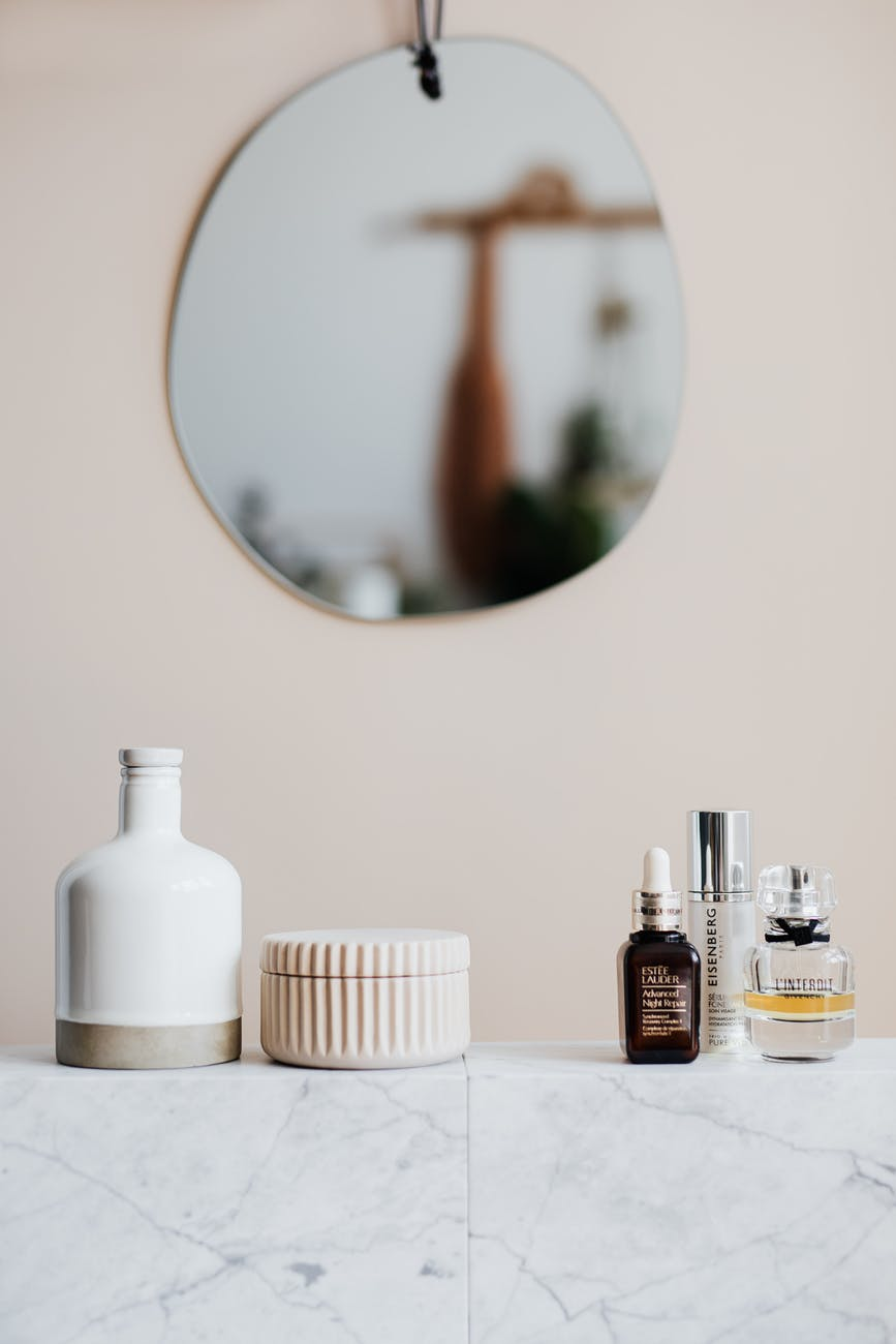 set of cosmetic products on marble shelf in modern room
