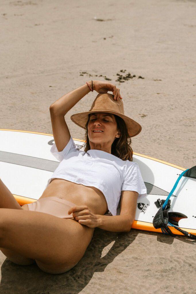 woman lying against a surfboard on the beach